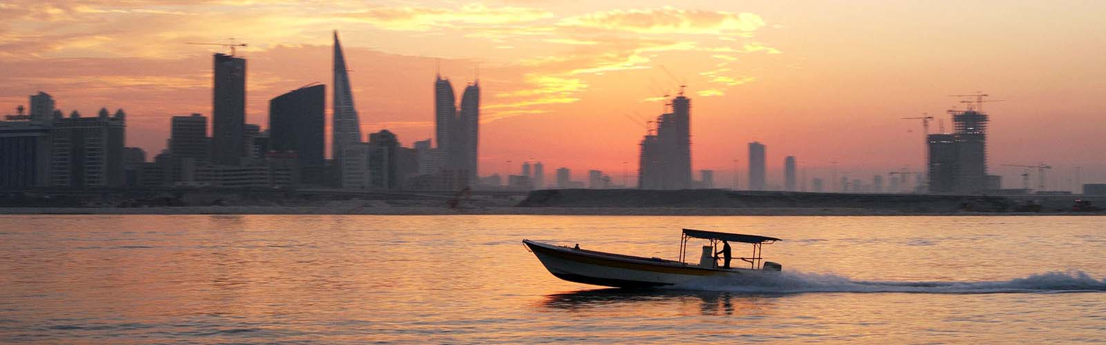 Boat sailing at sunset. Dubai skyline in the background